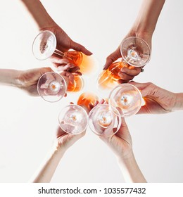 Girls Cheers. Hands with glasses of wine toasted, bottom view. Celebration, Success, Friends, 8 march hen-party Concept. Group of partying girls clinking flutes, close up. Flat lay Celebrate.