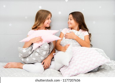 Girls children on bed with cute pillows. Pajamas party concept. Girls just want to have fun. Girlish secrets honest and sincere. Friends kids have nice time pleasant leisure. Best friends forever.