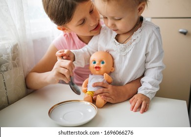 Girls children play with a doll, feed the doll from a spoon. The older sister is playing with the baby and the doll. Authentic lifestyle in a real interior