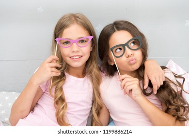 Girls children posing with grimaces photo booth props. Pajamas party concept. Girls friends having fun pajamas party. Friends cheerful posing with eyeglasses accessories for party. Playful mood.