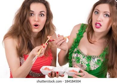 Girls with chopsticks eating sushi ginger