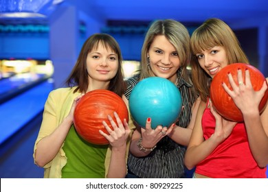 Girls closely stand alongside, hold balls for bowling and smile