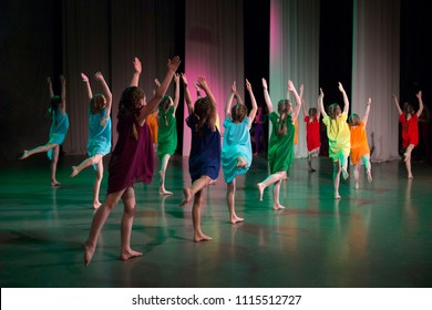 Girls in colorful dresses dance on stage barefoot.