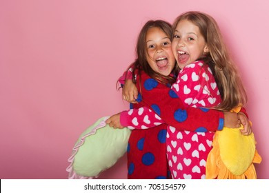 Girls in colorful polka dotted pajamas hold funny yellow and green pillows. Children with cheerful faces and loose hair hug. Kids stand on pink background, copy space. Childhood and happiness concept