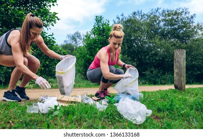 Girls crouching with garbage bag picking up trash doing plogging