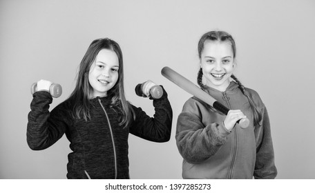 Girls cute kids with sport equipment dumbbells and baseball bat. We love sport. Child might excel in completely different sport. Friends ready for training. Ways to help kids find sport they enjoy.