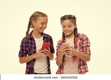 Girls cute small children smiling to phone screen. They like internet surfing social networks. Problem of young generation. Mobile phone and internet addiction or obsession. Mobile phone dependence.