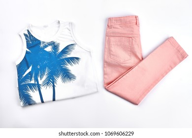 Girls cute summer cotton attire. White printed t-shirt and peach color trousers for young girl on white background.
