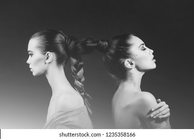 girls or cute women, fashion models, with braided or tied, beautiful, healthy, brunette, long hair into braid or plait on grey background. Friendship and friends