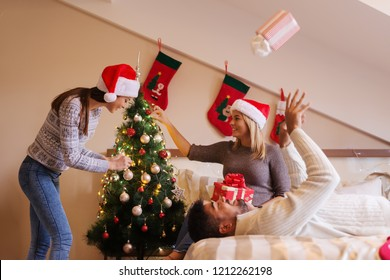 Girls decorating Christmas tree while their friend lying on bed and throwing gift up. Christmas holidays concept.