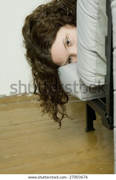 Girl`s  depressed. Girl`s face looking out from sofa. Teen`s problem