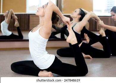 Girls doing yoga exercises in class, sitting in asana eka pada radzhakapotasana (One-Legged King Pigeon Pose) - hands grasps feet, instructor on the background coaching one of the yoga students
