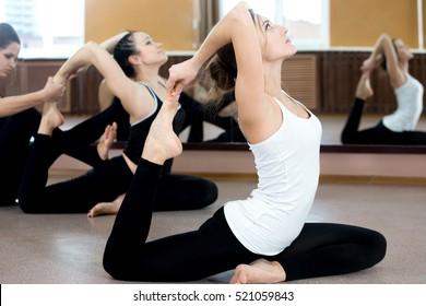 Girls doing yoga exercises in class, sitting in asana eka pada rajakapotasana (One Legged King Pigeon Pose), instructor on the background coaching one of the yoga students. Full length, side view