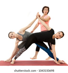 girls doing yoga under the guidance of a trainer
