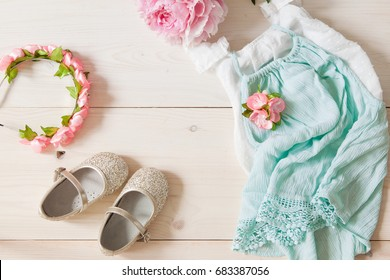 Girl's dress, floral tiara and shiny shoes on a wooden background. Girl's apparel for party, top view