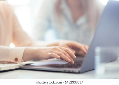 Girls dressed in casual discuss work issues, hands on a laptop