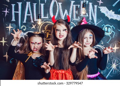 Girls, dressed up in Halloween costumes, show emotions of witches . Halloween party with group children.