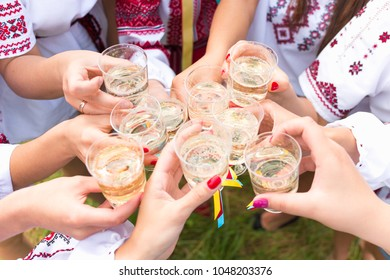 Girls dressed in Ukrainian traditional national attire clinking glasses at hen party outdoors