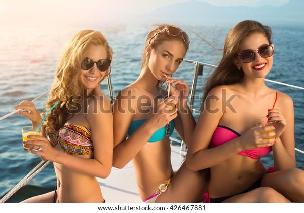 ヨットで飲み物を持つ女の子。水着を着た女性は微笑んでいる。若くて幸せ。美しい女性の明るいほほえみ。