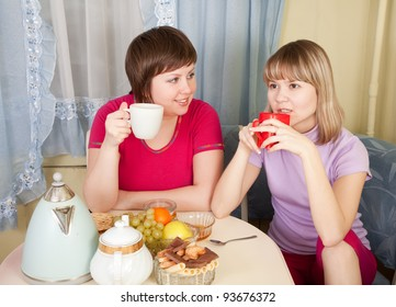 Girls  drinks tea and talking in the kitchen