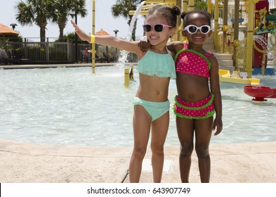 Girls embrace at pool by waterslide wearing sunglasses in summer