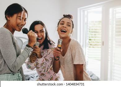 Girls enjoying and having fun singing songs holding microphones at home. Three young girls enjoying singing karaoke during a sleepover.