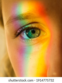 A girls eye at a closeup with a rainbow creative light across face. Young girl staring down camera with long lashes.