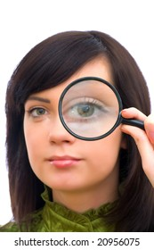 Girl's eye magnified through magnified glass on white