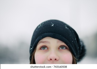 girl's eyes are looking up. Girl in a black beret. A child with beautiful green eyes against the background of a winter landscape.