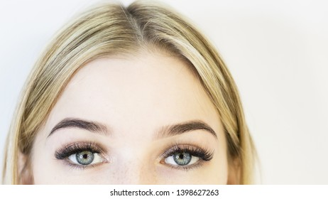 The girl's face is a blonde. Close-up. Facial care.