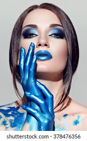 The girl's face with blue makeup with white paint. Hands painted in blue paint. Long straight black hair.