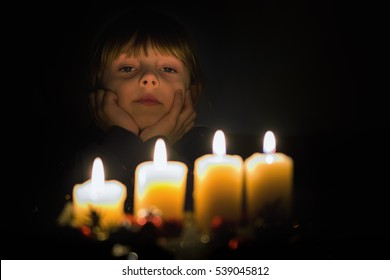 Girls face lit candle flame. Dark background, candles in the foreground.