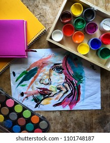 The girl's face is painted in watercolor. Wooden table, gouache, watercolor, notebooks. The working process.