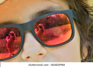 The girl's face and the reflection of a man with a camera in her sunglasses