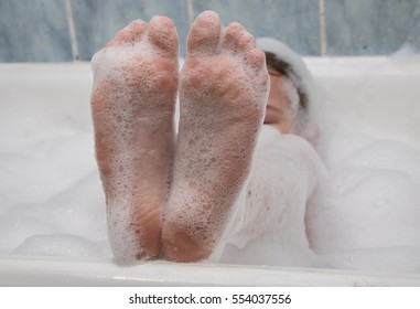 girl's feet legs that are wrinkled in the foam water.