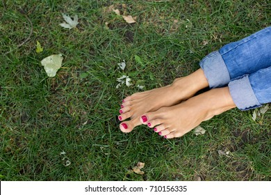 girls feet on grass in jeans. pedicure pink. women's legs. relax on the lawn. green grass
