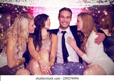 Girls flirting with young man against gold and red lights