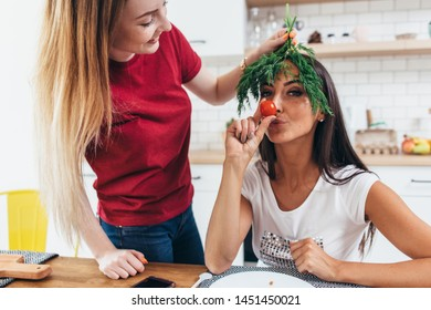 Girls fooling around in the kitchen playing with vegetables.