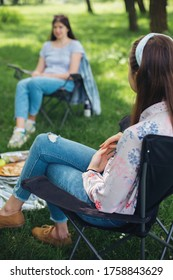 Girls Friends chilling among trees at picnic with social distance in summer park. Social distancing. Leisure activity together in new normal, safety gatherings. Young woman relaxing