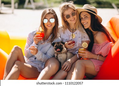 Girls friends with coctails sitting on pool mattress
