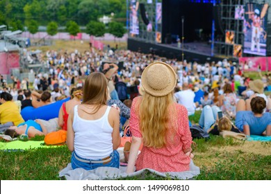 Girls friends watching concert at open air music festival, back view, stage and spectators at background