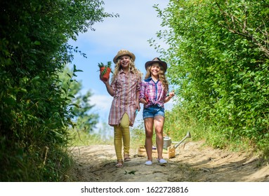 Girls with gardening tools. Agriculture concept. Adorable girls in hats going planting plants. Sisters helping at farm. On way to family farm. Kids siblings having fun at farm. Eco farming concept.