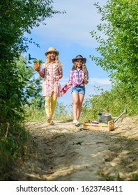 Girls with gardening tools. Sisters helping at farm. On way to family farm. Kids siblings having fun at farm. Eco farming concept. Agriculture concept. Adorable girls in hats going planting plants.