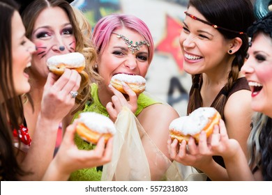 Girls at German Fasching Carnival eating doughnut-like traditional pastry