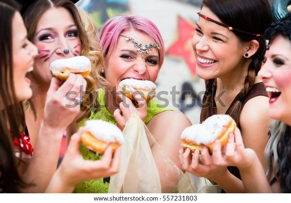 Mädchen auf der Fasching-Karnevalsfeier, die dughnusähnliches traditionelles Gebäck essen