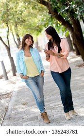 Girls going for a walk outdoors and looking at their mobile phone
