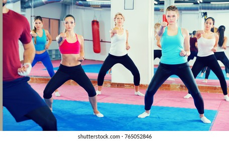 girl's group practicing self-defense with their coach in the gym