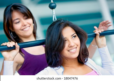 girls at the gym doing upper back machine exercises