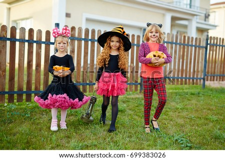 girls in halloween costumes walking from house to house and asking for treats