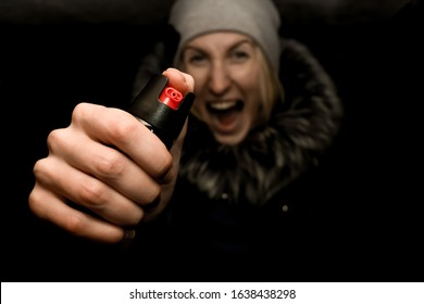 Girl's hand with a bottle of pepper spray close-up. In the background, a girl screams in the dark on the street. Protection from criminals.